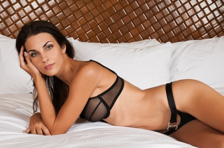 Beautiful slender brunette in sheer black lingerie photo