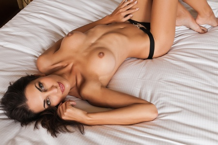Beautiful slender brunette lying topless in black panties Stock Photo - 11322011