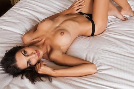 Beautiful slender brunette lying topless in black panties Stock Photo - 11322011