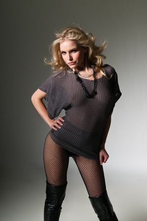 Pretty petite blonde in a gray sweater and fishnets Stock Photo - 11599787