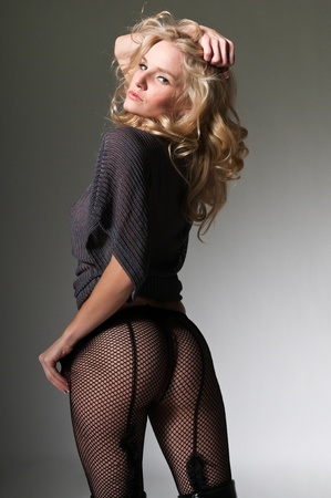 petite: Pretty petite blonde in a gray sweater and fishnets Stock Photo