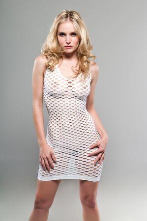 Mooie petite blonde in een wit net jurk