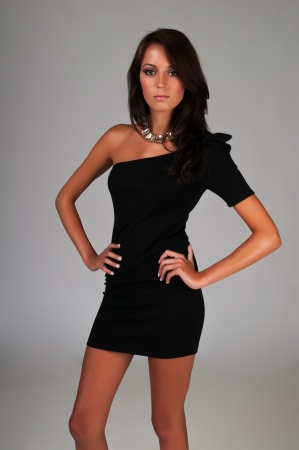 short dress: Beautiful slender brunette in a little black dress Stock Photo