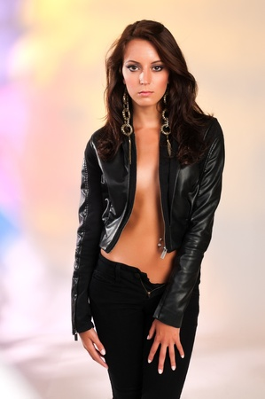Beautiful slender brunette in black leather photo