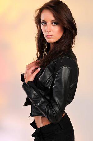 Beautiful slender brunette in black leather Imagens