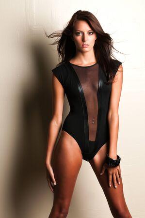 Beautiful slender brunette in a black leotard photo