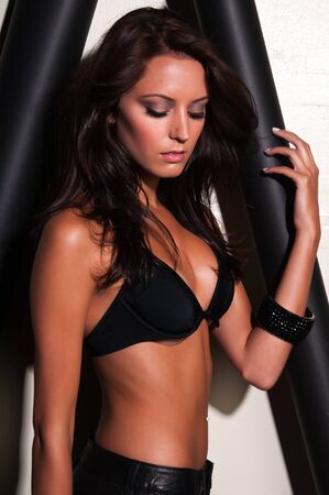 Beautiful slender brunette in a black bra and leather shorts photo