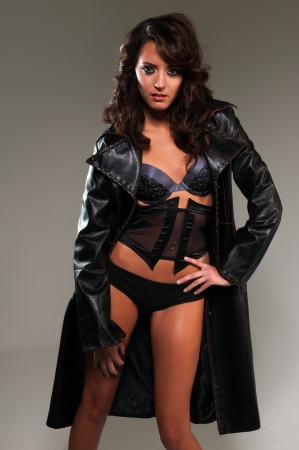 Beautiful young brunette in lingerie and trenchcoat photo