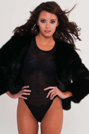 Beautiful young brunette in a leotard and fur coat photo