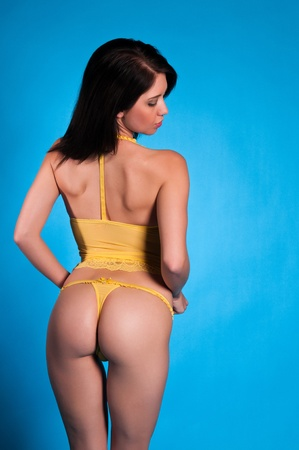 negligee: Beautiful young brunette dressed in yellow lingerie