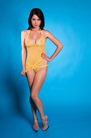 Beautiful young brunette dressed in yellow lingerie photo