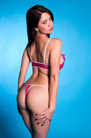 revealing: Beautiful young brunette dressed in pink lingerie