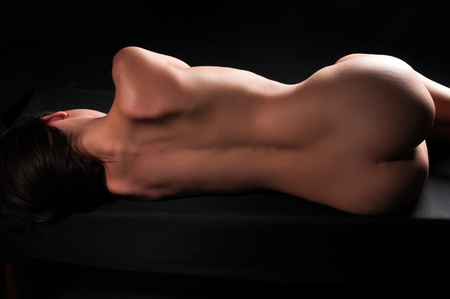naked woman back: Nude brunette lying on her side in deep shadow