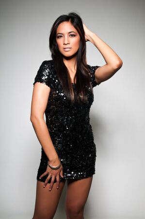 Pretty young Asian woman in a sequined black dress photo