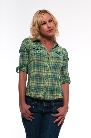 Pretty young blonde woman in a green plaid shirt and jeans
