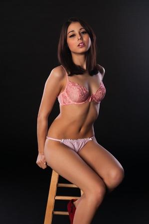 barstool: Pretty slender multiracial brunette in pink lingerie Stock Photo