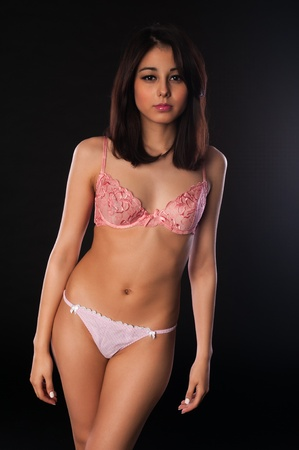 petite: Pretty slender multiracial brunette in pink lingerie Stock Photo