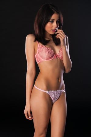 femme brune: Jolie mince multiraciale brune en lingerie rose Banque d'images