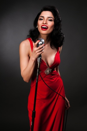 retro woman: Brunette chanteuse in a vintage red dress Stock Photo