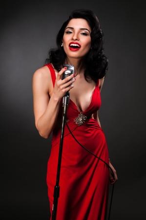 Brunette chanteuse in een vintage rode jurk