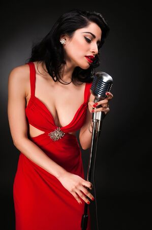 Brunette chanteuse in a vintage red dress Stock Photo