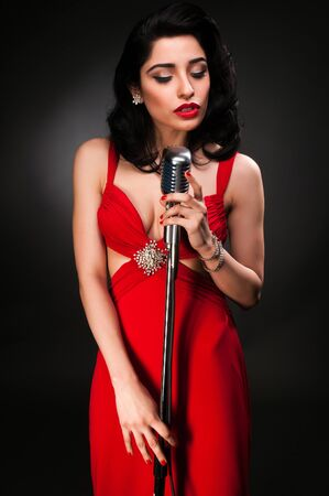 Brunette chanteuse in a vintage red dress photo