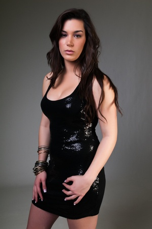 Pretty young brunette in a sequined black dress photo