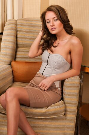strapless dress: Pretty young brunette sitting in a comfy chair