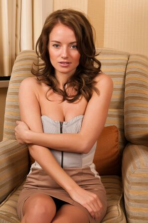 strapless: Pretty young brunette sitting in a comfy chair