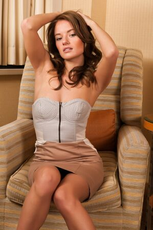 bodice: Pretty young brunette sitting in a comfy chair
