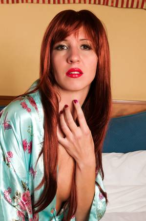 Beautiful slim redhead lying in bed photo