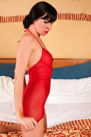 Beautiful slim brunette in a red camisole photo