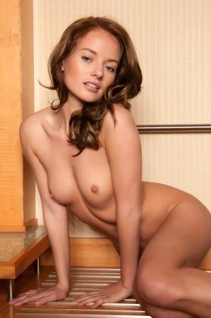 femme se deshabille: Belle jeune brune nue assise sur un porte-bagages