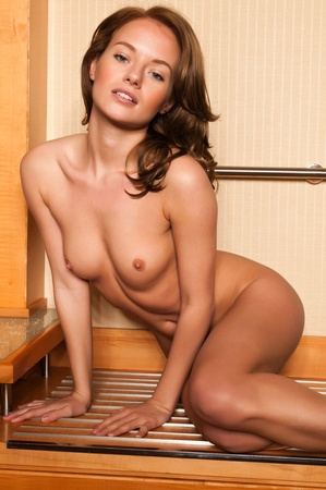 female nudity: Beautiful young brunette sitting nude on a luggage rack