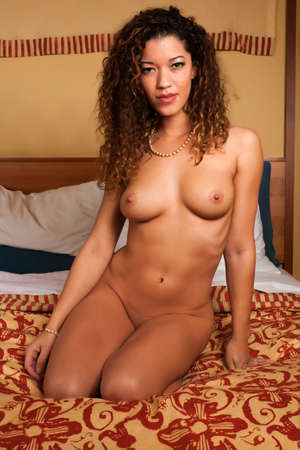 Beautiful multiracial woman sitting nude in bed photo