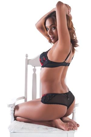 donna seduta sedia: Bella giovane donna multirazziale in lingerie rosso e nero