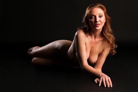 mujer desnuda: Hermosa rubia alta desnuda sobre un fondo negro Foto de archivo