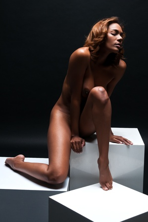 black girl nude: Beautiful young multiracial woman sitting nude on white cubes