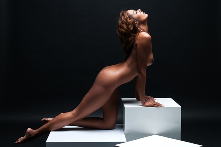 naked african: Beautiful young multiracial woman sitting nude on white cubes