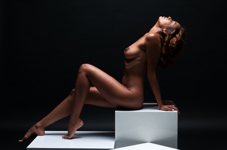 Beautiful young multiracial woman sitting nude on white cubes