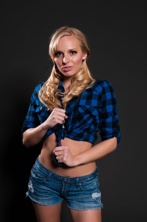 Blue eyed blonde in a plaid shirt and denim shorts