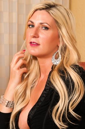 short dress: Beautiful mature blonde in a little black dress