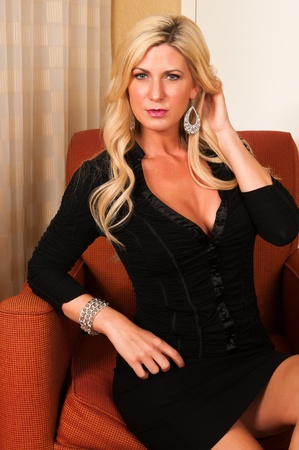 mujeres sentadas: Hermosa rubia madura en un pequeño vestido negro