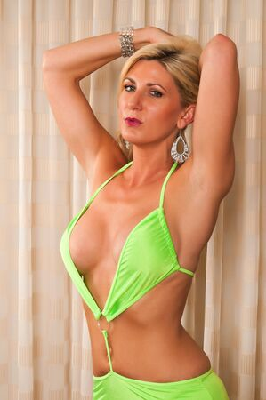 mature woman sexy: Beautiful mature blonde in a revealing lime green outfit Stock Photo