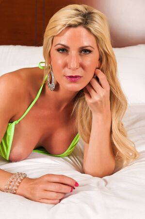Beautiful mature blonde in a revealing lime green outfit photo