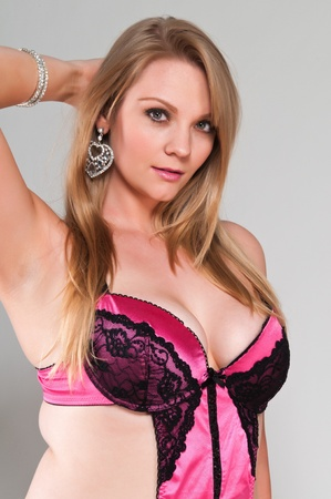 voluptuous women: Pretty young plus size blonde in pink lingerie Stock Photo