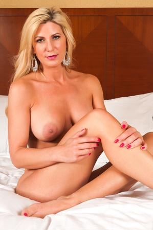 mujer desnuda sentada: Hermosa rubia madura desnuda en la cama
