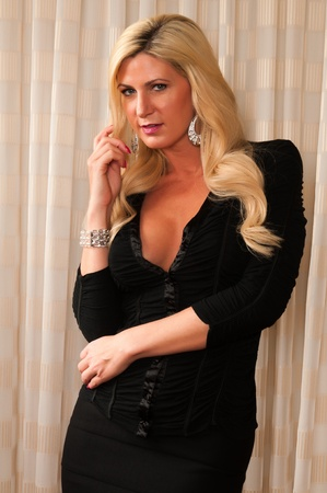 Beautiful mature blonde in a little black dress photo