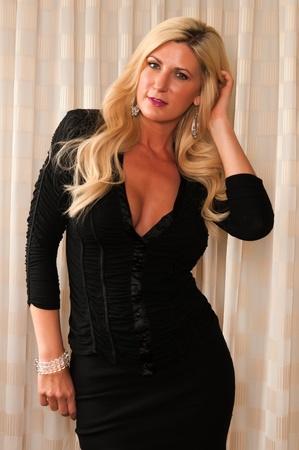 작은 검은 드레스에서 아름 다운 성숙한 금발