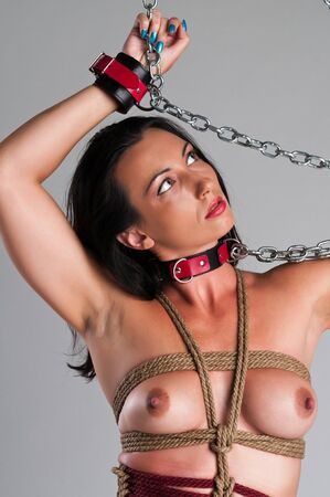 Athletic nude brunette bound with ropes and chains Stock Photo - 13335545